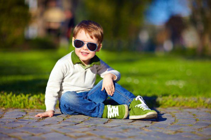 Мальчик в очках сидит на дорожке