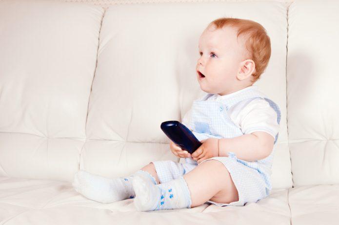 Маленький ребёнок на диване с пультом от телевизора