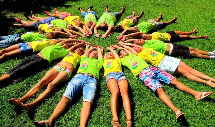 Дети в лагере лежат на траве