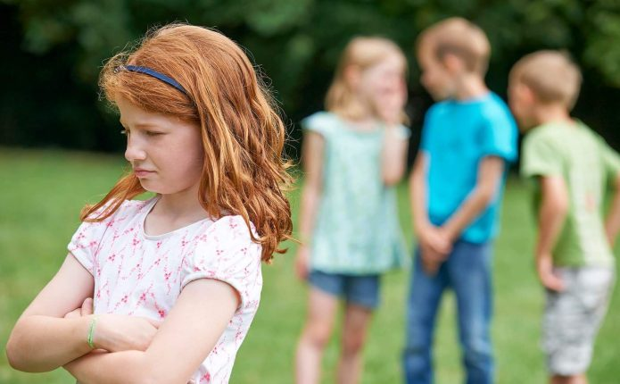Дети сплетничают за спиной у девочки