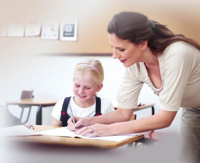 Учительница показывает ученице, как правильно выполнить задание