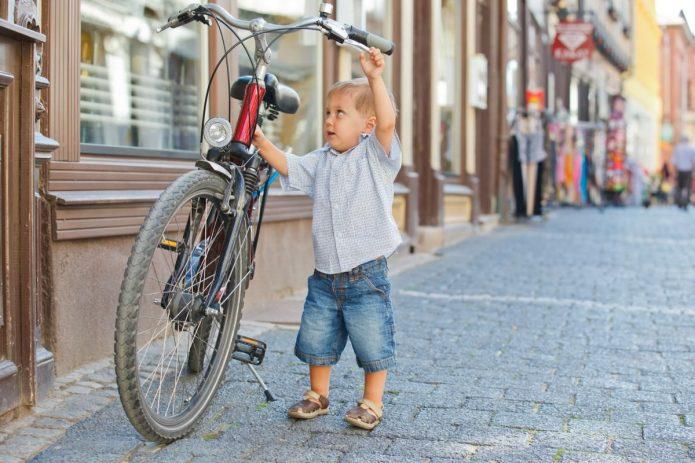Маленький мальчик возле большого велосипеда