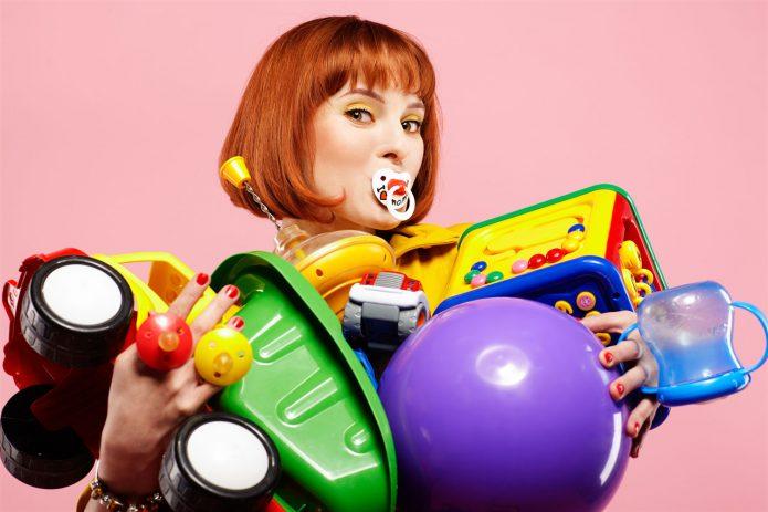 Женщина с игрушками в руках и пустышкой во рту