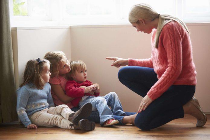 Женщина тычет пальцем в детей