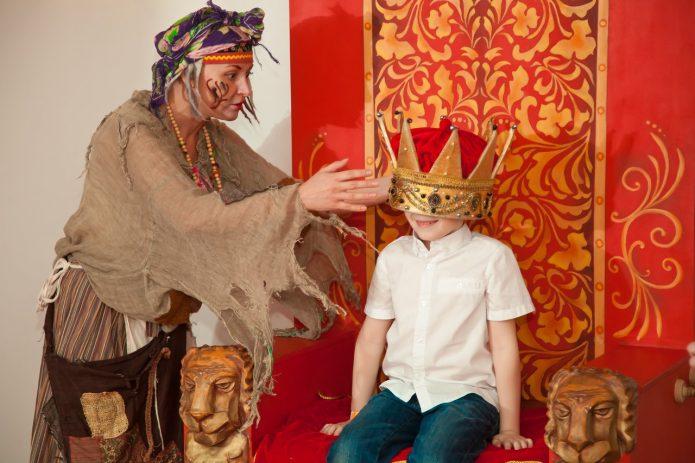 Ряженая женщина надевает на мальчика корону