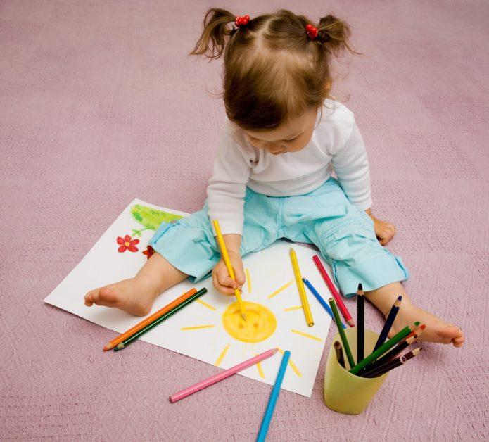 Девочка рисует сидя на полу