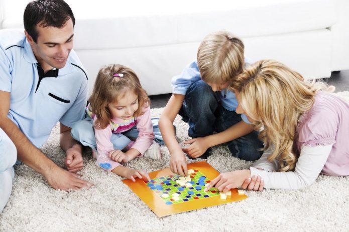Дети играют с родителями в настольную игру