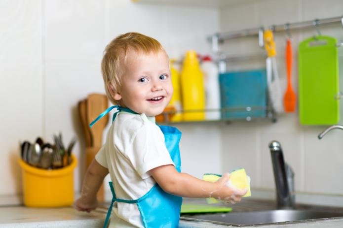 Малыш на кухне с губкой для посуды