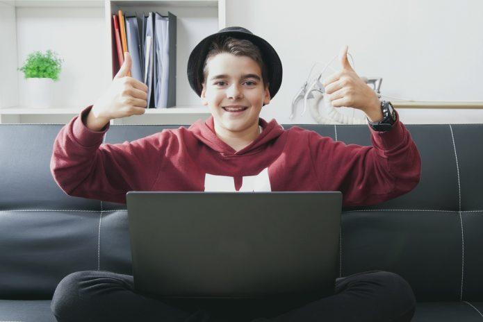 Подросток сидит перед ноутбуком, улыбается и жестикулирует