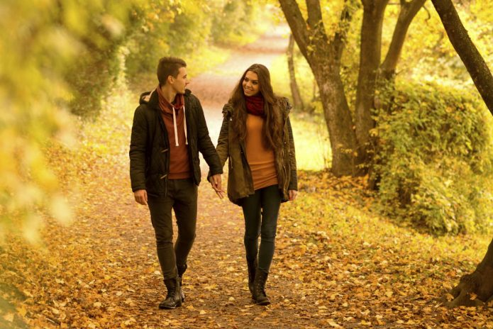 Влюблённые парень и девушка идут по парку
