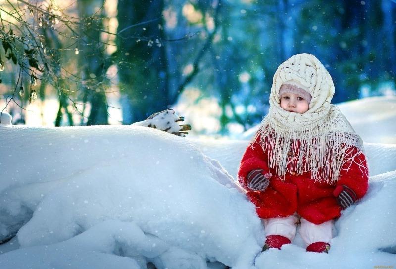 Девочка в платке сидит в сугробе
