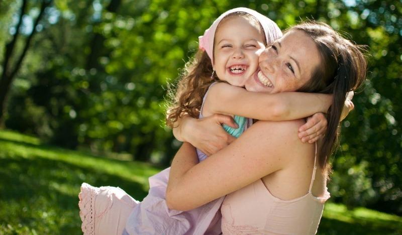 Девочка крепко обнимает маму за шею